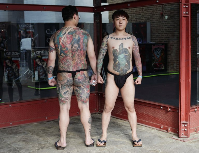 NOTE NUDITY  Meagan (left) and Seoyul, both from South Korea, attending the London International Tattoo Convention at Tobacco Dock in London. PRESS ASSOCIATION Photo. Picture date: Friday September 23, 2016. Photo credit should read: Yui Mok/PA Wire