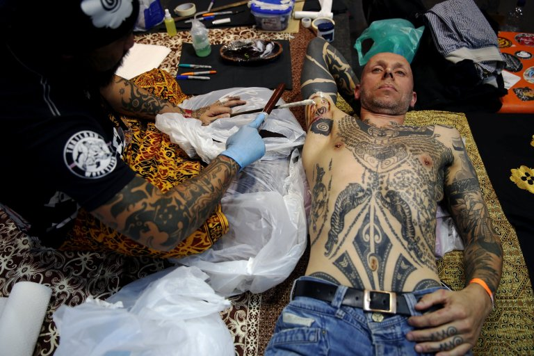 A man is tattooed at the International London Tattoo Convention in London, Britain September 23, 2016. REUTERS/Neil Hall