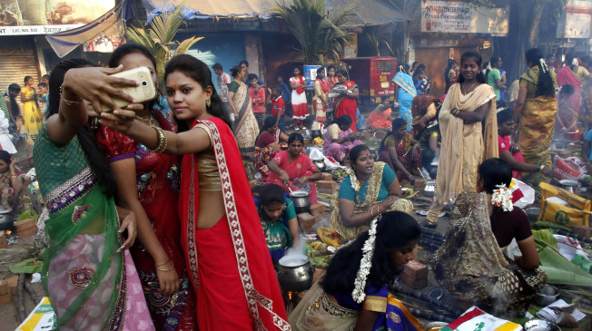 Indian Tamil Hindu women take selfies as they cook special food to celebrate the harvest festival of Pongal at Dharavi, one of the world's largest slums, in Mumbai, India, Friday, Jan 15, 2016. This celebration, held according to the solar calendar, marks the beginning of the sun's northward movement, considered to be auspicious. (AP Photo/Rajanish Kakade)
