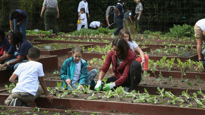 WASHINGTON, DC - APRIL 15:  First lady Michelle Obama and local students plant vegetables in the White House kitchen garden on the south lawn April 15, 2015 in Washington, DC. This is the seventh year in a row the first lady has planted a vegetable garden on the South Lawn to initiate a national conversation around healthy eating.  (Photo by Mark Wilson/Getty Images)