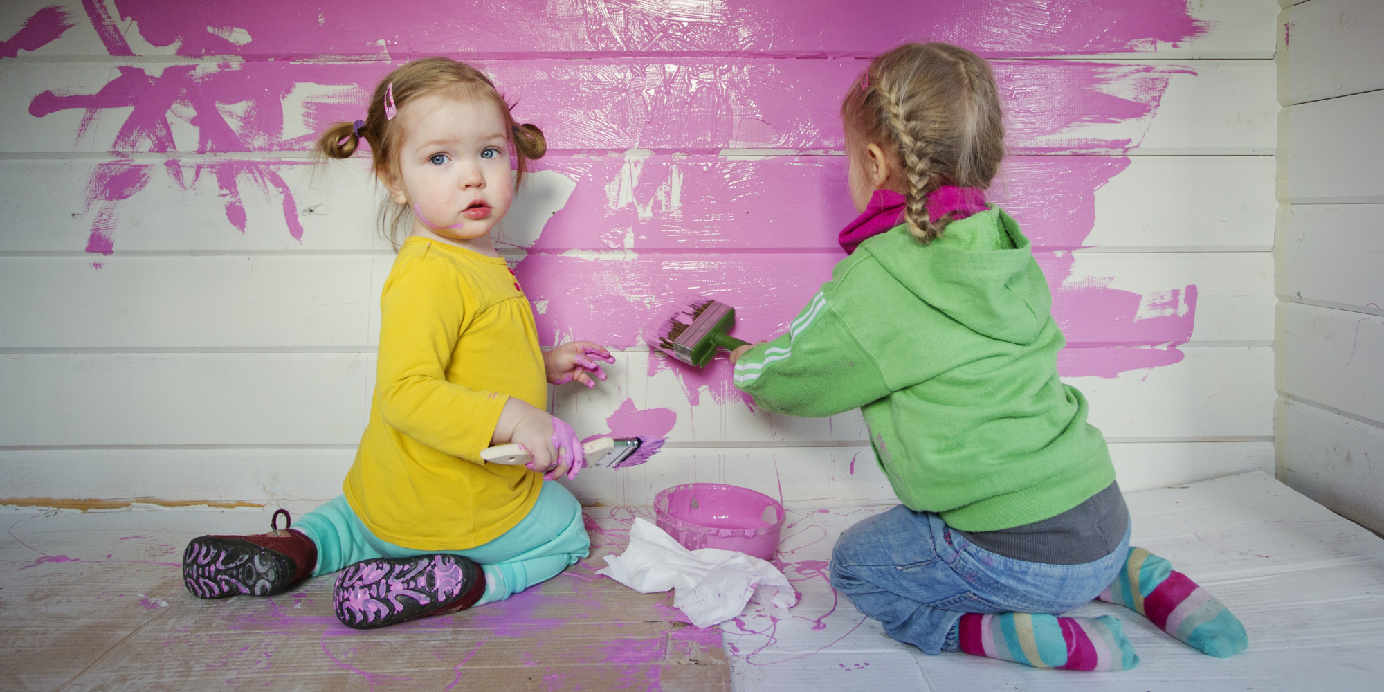Sisters, 1 years (facing the camera) and 3 years, painting a white wall pink.